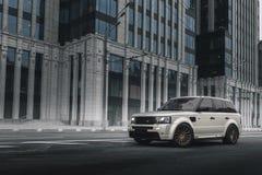 La tierra Rover Range Rover Sport del coche parqueó cerca del edificio moderno en Moscú en el d3ia Imágenes de archivo libres de regalías