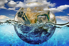 La tierra se sumerge en agua, entre las nubes contra el cielo. Elementos de esta imagen equipados por la NASA Fotos de archivo libres de regalías