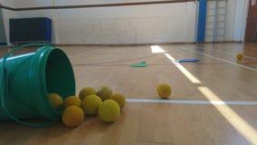 La tina verde de pelotas de tenis de los gorrones dispersó en el piso del gimnasio Imagenes de archivo