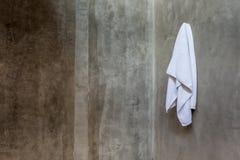 La toalla blanca colgante cubrió en el muro de cemento expuesto en el bathr fotografía de archivo