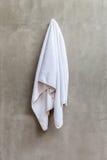 La toalla blanca está colgando en el muro de cemento expuesto en el bathr foto de archivo