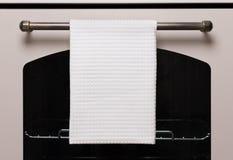 La toalla de cocina blanca cuelga en la manija del horno, maqueta del producto foto de archivo