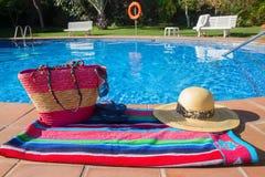 La toalla y los accesorios del baño acercan a la piscina Imagen de archivo