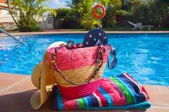 La toalla y los accesorios del baño acercan a la piscina Foto de archivo libre de regalías