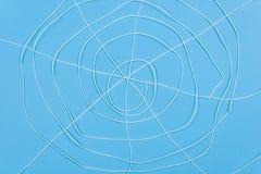 La toile d'araignée abstraite, blanc filète le fond bleu Images libres de droits