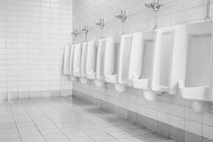 La toilette de l'homme avec la vue de toilette par des urinoirs, intérieure au vieux fond de toilette dans le ton noir et blanc Photo stock