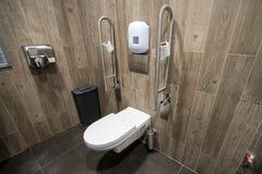 La toilette per gli anziani di disattiva la gente con il corrimano sul lato immagini stock