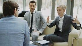 La toma panorámica tiró de la empresaria que hablaba y duscussing con los colegas masculinos del negocio que se sentaban en el so