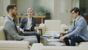 La toma panorámica tiró del hombre de negocios que discutía informes financieros con los socios comerciales femeninos y masculino