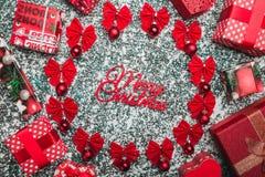 La tomaia, cima, vista da sopra di un'iscrizione di Buon Natale dentro di un cerchio ha creato dagli archi rossi e dai bordi semp Fotografia Stock Libera da Diritti