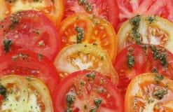 La tomate découpe le fond en tranches Photo libre de droits