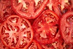La tomate découpe le fond en tranches Image libre de droits