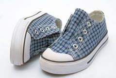 La tonalità blu scherza le scarpe di sport di paia delle scarpe da tennis su bianco Immagine Stock