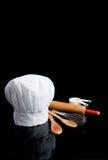 La toque d'un chef avec des ustensiles de cuisine sur le noir Images libres de droits