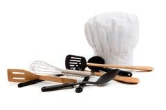 La toque du chef avec de diverses batteries de cuisine Photographie stock libre de droits
