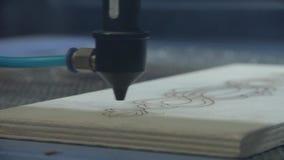 La torcia del laser sta tagliando un piatto del compensato Fascio di taglio del laser sopra lo strato del compensato video d archivio