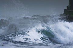 La tormenta del mar agita dramáticamente estrellarse y salpicar contra rocas Foto de archivo