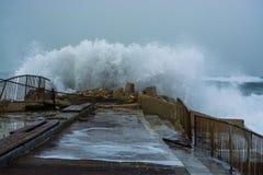 La tormenta del mar agita estrellarse y salpicar contra el embarcadero Foto de archivo