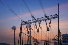 La torre ad alta tensione della trasmissione nel tramonto Immagine Stock Libera da Diritti