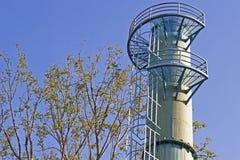 La torre de agua y el cielo azul es árbol cercano Imagen de archivo libre de regalías
