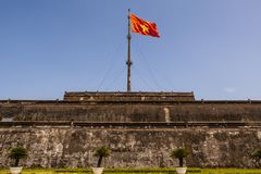 La torre de la bandera con la pieza vietnamita de Nguyen Dynasty de la bandera de la ciudadela en tonalidad, la capital antigua d foto de archivo