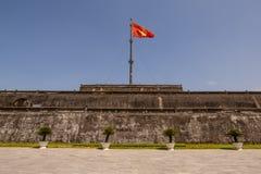 La torre de la bandera con la pieza vietnamita de Nguyen Dynasty de la bandera de la ciudadela en tonalidad, la capital antigua d imagen de archivo libre de regalías