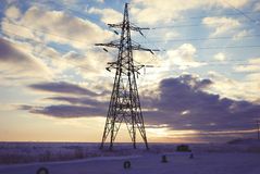La torre de la electricidad en la tarde se nubla el fondo en el invierno fotografía de archivo