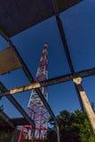La torre de las telecomunicaciones de estructuras abandonadas contra noche protagoniza Imagen de archivo