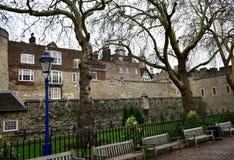La torre de Londres con una farola azul y de oro, árboles y bancos de madera Londres, Reino Unido foto de archivo