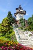 La torre de reloj (el Uhrturm) y jardín de flores Graz, Austria Imagenes de archivo