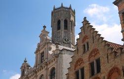 La torre del campanile e dei tetti antichi di Bruges e un giorno soleggiato belgium immagine stock libera da diritti