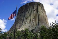 La torre del diablo con la bandera americana Imagenes de archivo