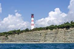 La torre del faro su una spiaggia ripida immagine stock