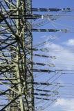La torre della trasmissione, vista parziale di un'alta tensione della sottostazione con molte linee contro un cielo blu con nebbi Fotografia Stock