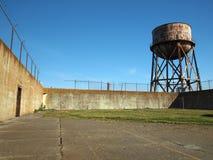 La torre di acqua d'arrugginimento sta oltre il recinto di filo metallico del bardo e della parete Immagine Stock