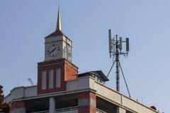 La torre di orologio è su una costruzione arancio fotografie stock libere da diritti