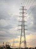 La torre ed il cavo ad alta tensione allineano con le nuvole di pioggia Immagine Stock