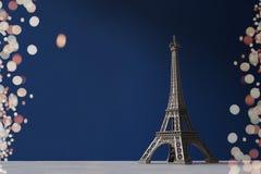 La torre Eiffel del recuerdo en un fondo azul con el bokeh colorido se enciende como marco Fotos de archivo