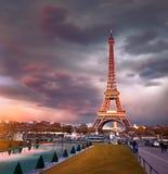 La torre Eiffel en una puesta del sol mitad-se encendió con los rayos pasados del ajuste foto de archivo
