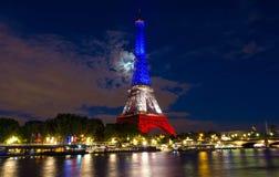 La torre Eiffel se encendió para arriba con los colores de la bandera nacional francesa Imagenes de archivo