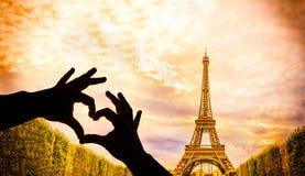 La torre Eiffel y las manos en un corazón forman Foto de archivo libre de regalías