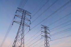 La torre eléctrica con el alambre en silueta negra en madrugada, enfoca adentro Imagen de archivo libre de regalías