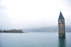 La torre sumergida de la iglesia del reschensee profundamente en el lago Resias de Bolzano o bozen en Italia imagen de archivo