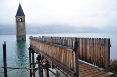 La torre sumergida de la iglesia del reschensee profundamente en el lago Resias de Bolzano o bozen en Italia fotografía de archivo