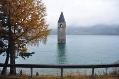 La torre sumergida de la iglesia del reschensee profundamente en el lago Resias de Bolzano o bozen, Italia fotografía de archivo