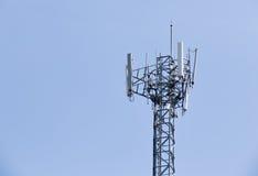 La torretta del telefono delle cellule aumenta contro un cielo blu Fotografia Stock