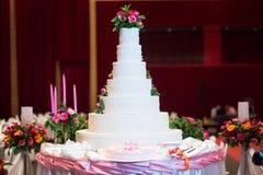 La torta adorna con la rosa, la flor y la vela del rosa para la ceremonia de boda Imagen de archivo libre de regalías