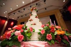 La torta adorna con la rosa, la flor y la vela del rosa para la ceremonia de boda Foto de archivo
