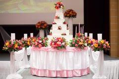 La torta adorna con la rosa, la flor y la vela del rosa para la ceremonia de boda Imagen de archivo