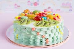La torta colorida con la fruta y los caramelos para los niños van de fiesta Imágenes de archivo libres de regalías